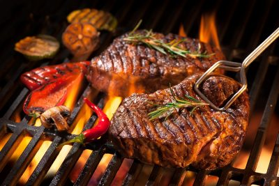Beef steaks on the grill with flames - Los Angeles Wolf Appliance Servicing