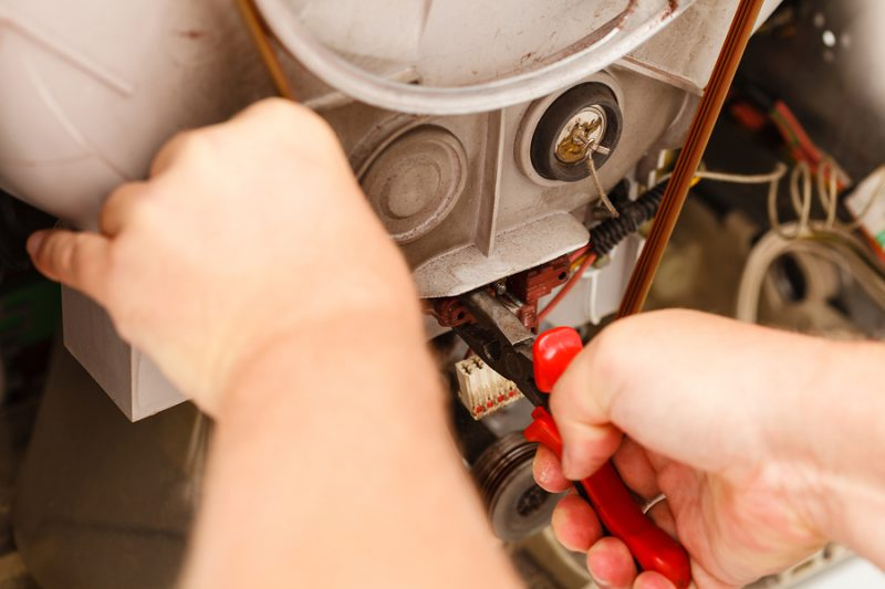 Domestic mechanical industrial concept. Mechanic repairing washing machine. Person using tools to fix broken device.