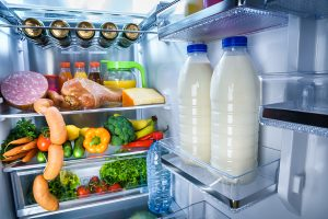 Open refrigerator filled with food. Focus on Bottles of milk in the fridge
