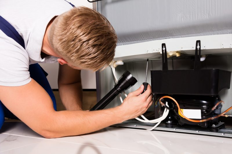 Young Male Technician Checking Refrigerator With Screwdriver - Las Vegas Sub-Zero appliance repair
