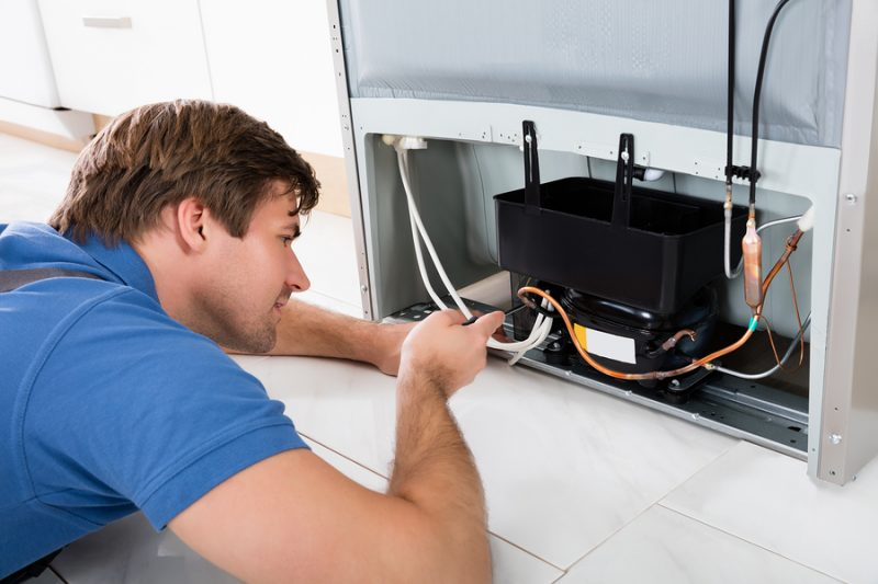 Close-up Of A Technician Repairing Refrigerator In Kitchen - Los Angeles Sub-Zero refrigerator repair