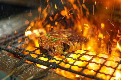 Beef steaks on the grill with flames. Grilled meat in barbecue with flames and coals. Grill meat. Empty Hot Charcoal Barbecue Grill With Bright Flame On The Black Background. - Orange County Asko appliance repair
