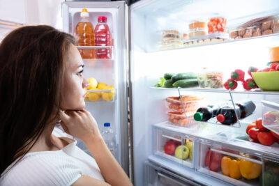 woman staring inside refrigerator