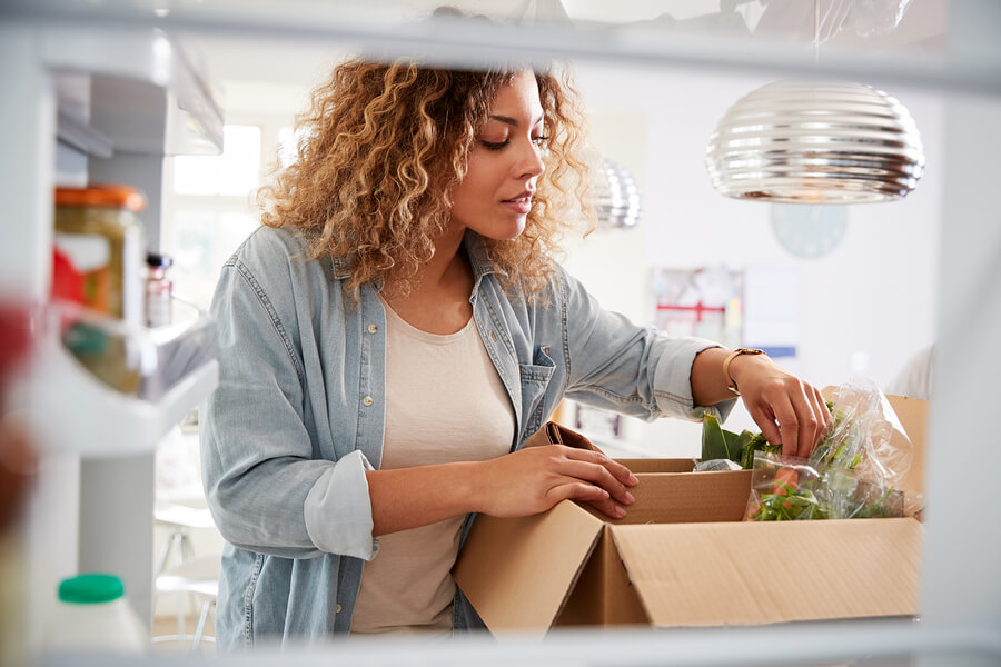 Woman-unpacks-online-home-food-delivery-in-refrigerator