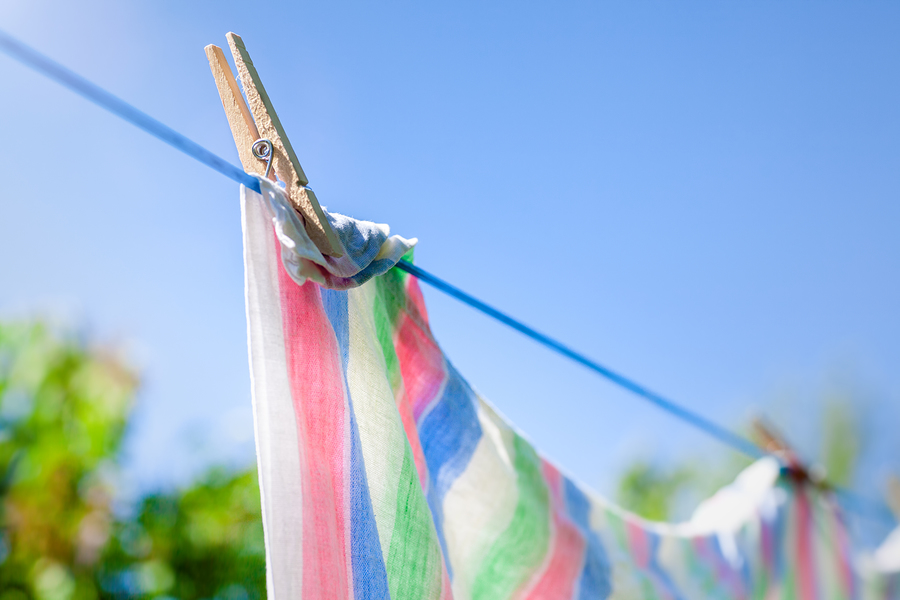 Freshly washed towels or sheets hanging to dry on a clothes line.