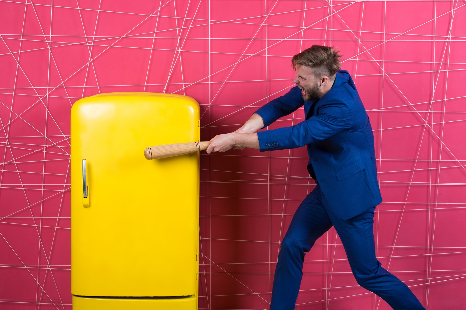 yellow-refrigerator-with-man-hitting-it-with-a-baseball-bat